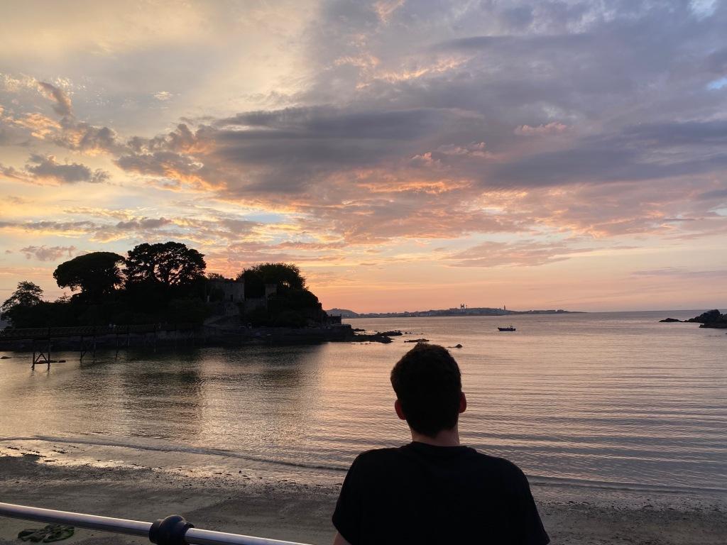 puesta de sol sobre el mar con el cielo de color rojizo. A la derecha se recorta la silueta de un chico que está de espaldas y a la izquierda la de una isla
