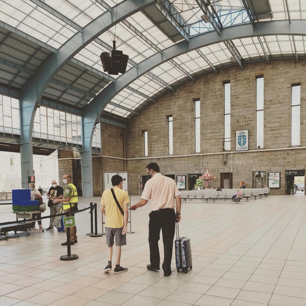 Un adolescente y un hombre adulto que se alejan juntos en una estación de tren hacia la zona de embarque. La foto está tomada de espaldas.